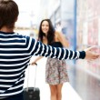 Stock Photo: Young man meeting his girlfriend with opened arms at airport arr