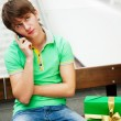 Portrait of young man inside shopping mall with gift box sitting — Stock Photo #8663967