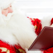 Santa sitting at home and reading a book. Indoors — Stock Photo