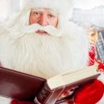 Santa sitting at home and reading a book. Indoors — Stock Photo