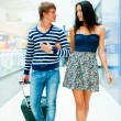Portrait of young couple walking together at airport hall with t — Stock Photo #8664040