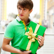 Portrait of young man inside shopping mall with gift box standin — Stock fotografie