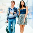Portrait of young couple walking together at airport hall with t - Stock Photo