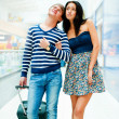 Portrait of young couple walking together at airport hall with t — Stock Photo #8664054