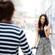 Young man meeting his girlfriend with opened arms at airport arr — Stock Photo #8664057