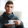 Portrait of a young man drinking coffee while sitting on armchai — Stock Photo #8664093