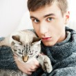 Relaxed man sitting on armchair holding and petting pet cat — Stock Photo #8664129