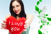 Cute young woman holds a heart symbol against beautiful background — Stock Photo