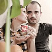 Atraktivní mladý dospělý pár sedící blízko na dřevěnou podlahu v — Stock fotografie