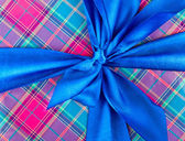 Big blue holiday bow on ornamental background — Stock Photo
