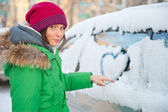 Beauty woman in the winter clothes drawing heart on car — Stock Photo