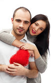 Happy young adult couple with red heart on white background — Stock Photo