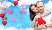 Happy young adult couple with red heart on romantic background — Stock Photo