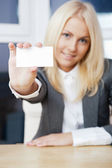 Young businesswoman showing her business card - sitting at her o — Stock Photo
