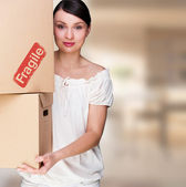 Closeup portrait of a young woman with boxes moving to her new home — Stock Photo
