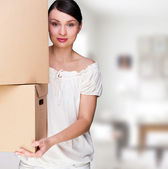 Smiling woman holding boxes after moving looking at the camera — Stock Photo