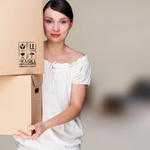 Closeup portrait of a young woman with boxes moving to her new h — Stock Photo