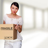 A woman holding a box inside office building or home interior. P — Stock Photo