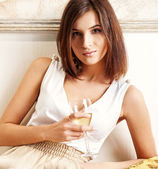 Elegant woman with champagne flute. Photo of beige warm colors — Stock Photo