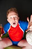 Jeune homme tenant bière et ballon de foot et de regarder la tv translati — Photo