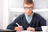 High school - Young male student write notes in classroom — Stockfoto