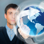 Portrait of handsome young man touching virtual globe. Global ne — Stock Photo
