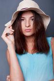 Sebevědomá žena se zbraní u její hlavy hospodářství klobouk proti přikrý — Stock fotografie