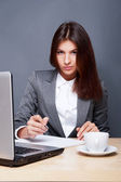 A pretty concentrated woman working with her laptop and papers. — Stock Photo