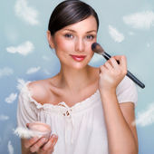 Portrait of a Beautiful woman applying makeup with brush on her — Stock Photo