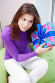 Delighted woman opening a gift sitting on the bean bag at home — Stock Photo