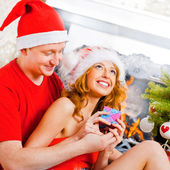 Young happy couple near a Christmas tree at home holding gift an — Stock Photo
