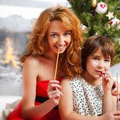Madre y su hija sentados juntos cerca de árbol de navidad — Foto de Stock