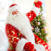 Santa sitting at the Christmas tree, near fireplace and looking — Stok fotoğraf