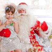 Christmas theme: Santa Claus and little girl having a fun. — Stock Photo
