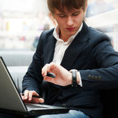 Portrait of handsome young man working with laptop at cafe at bu — Stok fotoğraf