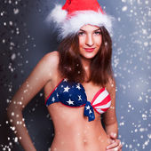 20-25 years old beautiful woman in christmas hat and swimsuit wi — Stock Photo
