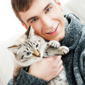 Relaxed man sitting on armchair holding and petting pet cat — Stock Photo
