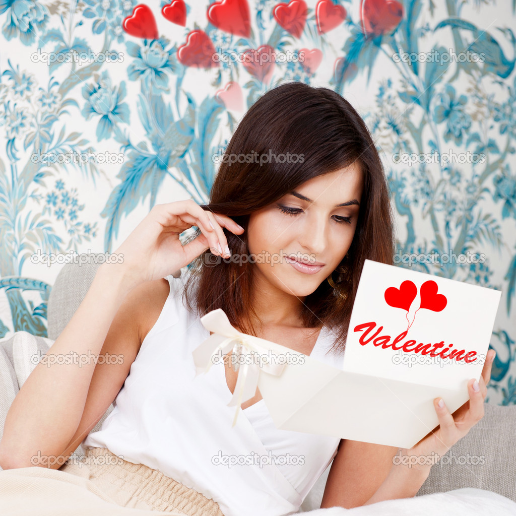 Portrait of young attractive happy woman, reading valentine card while sitting on comfortable sofa at living room at her home — Stock Photo #8661853