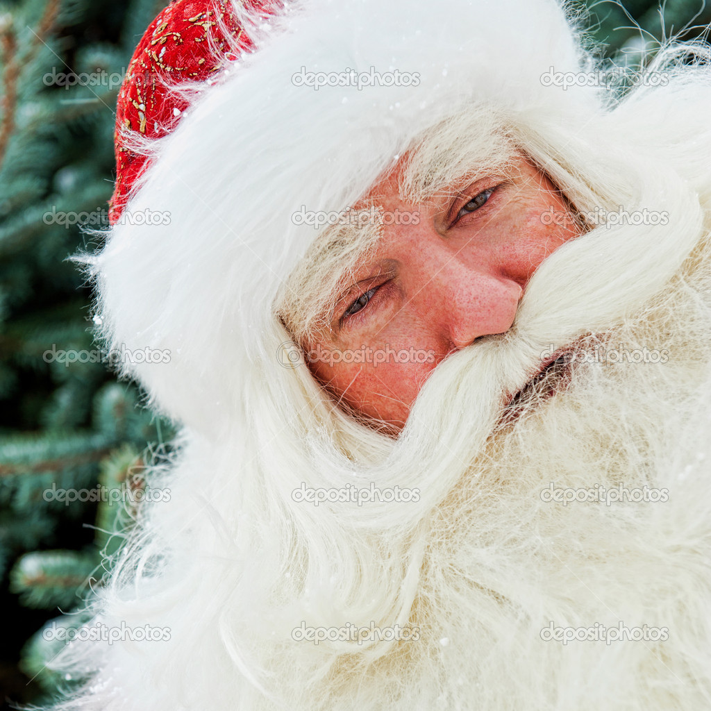 Portrait of Santa Claus standing with hand on chin outdoors at christmas tree. Snow falls. Natural light — Stock Photo #8663814