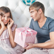 Young happy couple presenting gift in bed — Stock Photo