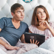 Young lively couple using tablet PC in their bed and daydreaming - Stock Photo