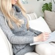 Pretty woman on sofa educating, holding copybook in her arms - Stock Photo