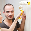 Happy smiling couple painting interior wall of home and having f — Stock Photo #8768216