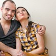 Attractive young adult couple sitting close on floor in home smi — Stock Photo #8768229