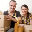 Young Couple with boxes in the new apartment sitting on floor an — Stock Photo #8768230