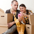Young Couple with boxes in the new apartment sitting on floor an — Stock Photo #8768234