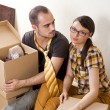 Young Couple with boxes in the new apartment sitting on floor an — Stock Photo