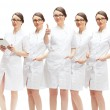 Portrait of young pretty doctor thumbs up with her clones in dif — Stock Photo
