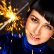 Portrait of young attractive celebrating woman holding sparkles - 
