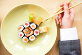 Top view of young business woman wearing suit holding sushi stic — Stock Photo